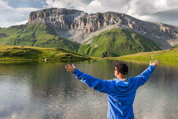 Man with raised hands standing on the shore of a mountain lake and enjoy the view