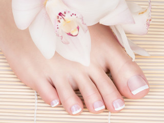 female feet with white french pedicure on nails. at spa salon