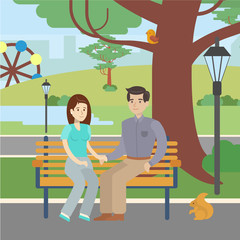 Couple in park. Happy man and woman sitting together at the bench and relaxing in the park.