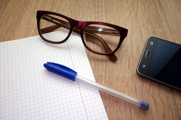 Working table with notebook, pen, glasses and smartphone