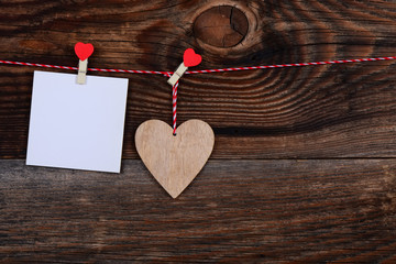 Heart and a blank sheet of paper on a beautiful old wooden background as love concept for valentines day