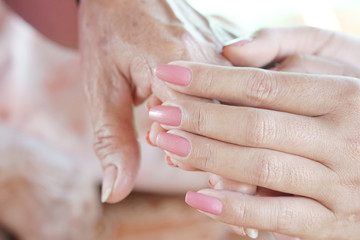 close-up of a woman holding an elderly woman's hand