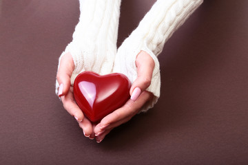 Female hands giving red heart, isolated on brown background