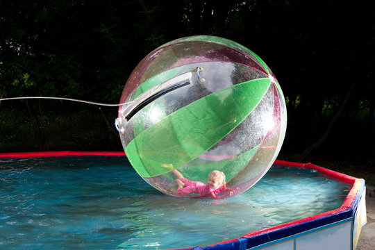 little girl in Zorb in the pool
