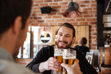 View from back of man clinking glasses with friend
