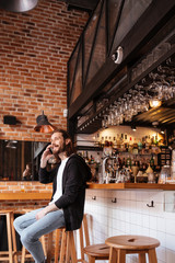 Vertical image of man sitting on bar