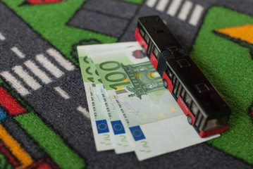 Toy bus parked on three 100 euro bills with street themed carpet, transportation costs concept