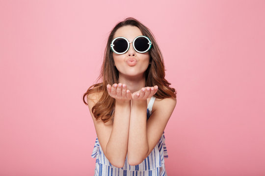 Cute young woman in round sunglasses standing and sending kiss