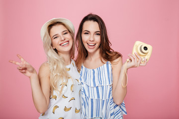 Two cheerful lovely young women standing and holding photo camera