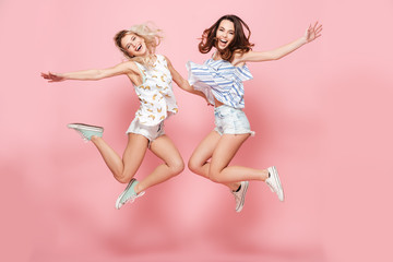 Two happy joyful young women jumping and laughing together Wall mural