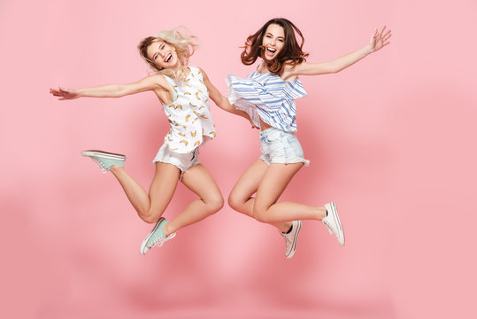 Two happy joyful young women jumping and laughing together