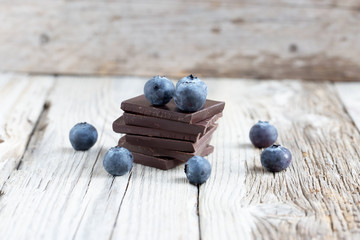 Dark chocolate stack and fresh organic blueberries on wooden table. Natural light, selective focus.