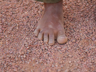 dirty children's foot is in the desert sand