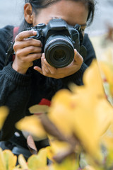 Woman with camera on meadow. Girl photographs of yellow flowers.