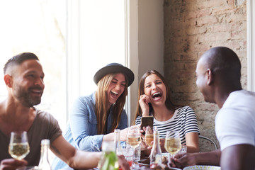 Friends laughing at something on phone at dinner