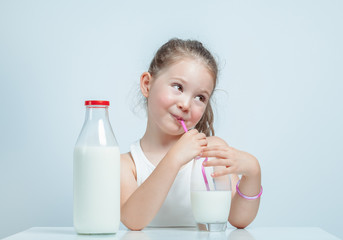 beautiful cute little girl drinking milk with straw