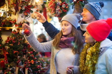middle-aged family couple with teen girl choosing Christmas deco
