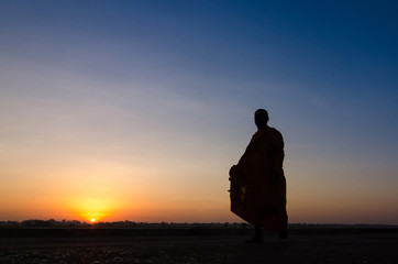 Silhouette of monk feet walking on concrete ground for people of