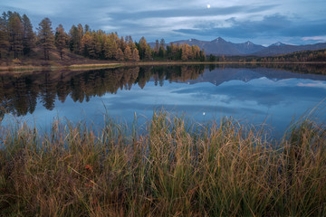 Mirror Surface Lake Autumn Landscape With Mountain Range On Background And Early Evening Moon