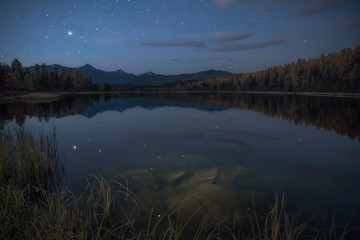 Mirror Surface Lake Autumn Landscape With Mountain Range In Early Eveing With Stars On The Sky