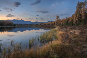 Mirror Surface Lake Autumn Landscape With Mountain Range On Background With Light Pink Sky