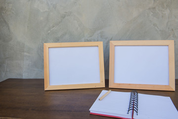 Two photo Frame on a wooden table and book on Gray wall background .