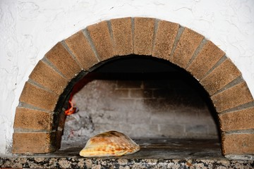 Freshly cooked Calzone in a wood fired oven, Crete.
