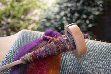 This is a photo of a drop spindle wrapped with handmade yarn on a pile of colorful wool sheep roving and blending board.