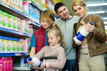 Happy family of four buying pasteurized milk