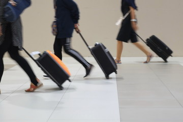 Blur and movement of people dragging suitcases in hurry.