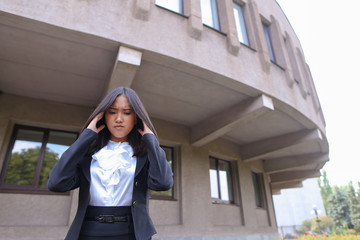 Pretty young asian business woman, student holds on head from fa
