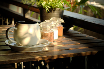 white cup of coffee with sugar on wooden table in the morning background