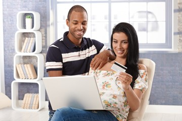 Diverse couple e-shopping at home
