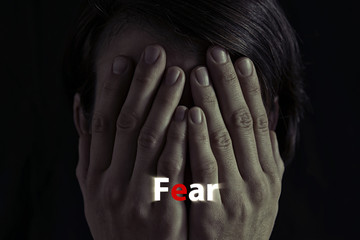 """Concept of fear, domestic violence. Woman covers her face her hands. Dim light and black  background , creates a dramatic mood of this  image. On image there is  inscription """"fear""""."""