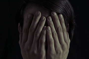 Wall Mural - Concept of fear, domestic violence. Woman covers her face her hands. Dim light and black  background , creates a dramatic mood of this  image.