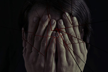 Concept of fear, domestic violence. Woman covers her face her hands. Image cut into many pieces for more drama.
