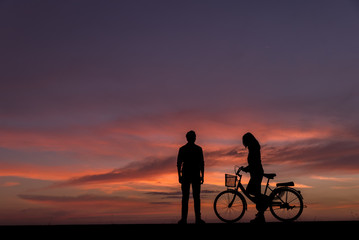 Silhouette of lovers standing  with vintage bikes on the side.The background image is a sunset in Thailand.