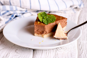 Chocolate cheesecake, decorated mint on a white plate