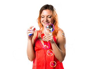 Beautiful woman with orange hair blowing bubbles