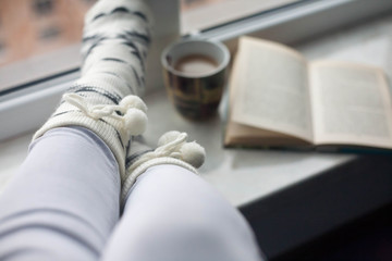 Female legs with hot drink and book
