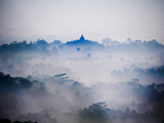 The sun rises on a foggy morning over Borobudur temple near Yogyakarta, Indonesia.