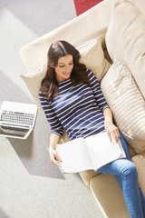 Lovely young woman reading a magazine while relaxing on couch at home