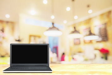 Laptop on wooden table over blurred photo of beautiful coffee shop for background use