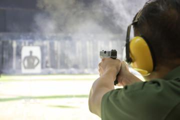 man firing automatic  pistol to target in shooting range