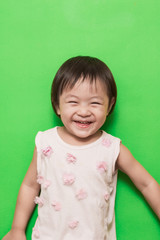Happy asian girl smiling on green background