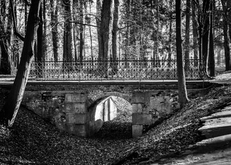 Old stone bridge with metal railing in a park. Black and white photo.