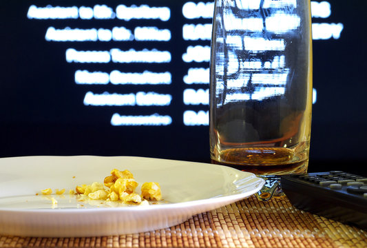 popcorn and coke leftovers and tv remote after watching movie,shallow depth of field