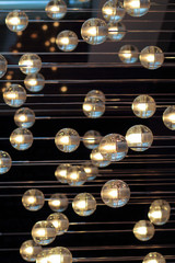 lighting balls on the chandelier in the lamplight,  light bulbs hanging from the ceiling, lamps on the dark background, selective focus, horizontal.