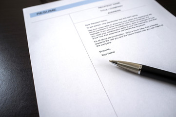 Close-up of resume and pen on table.