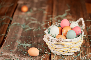 Easter basket and raw eggs on wooden table